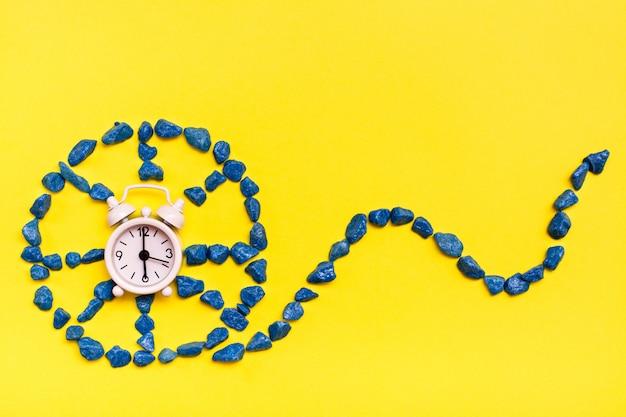 Despertador branco no centro da roda feita de pedras decorativas em um fundo amarelo. conceito de tempo vazando