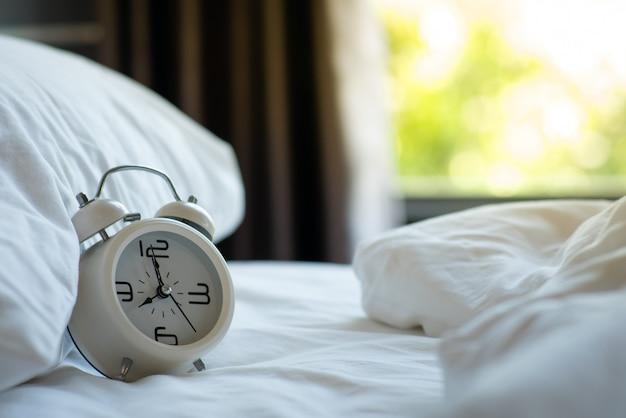 Despertador branco retrô no colchão branco no quarto