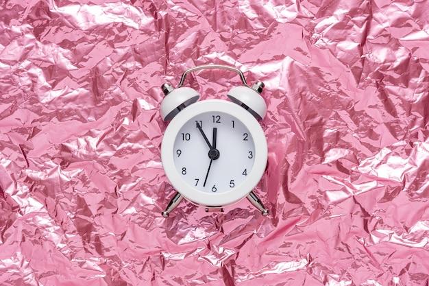 Despertador branco sobre fundo rosa de folha amassada.