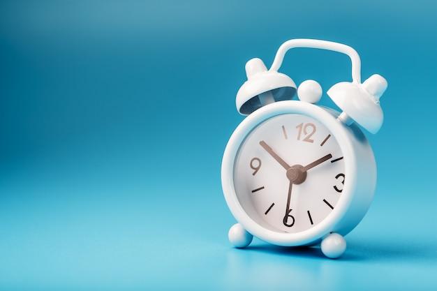 Despertador branco sobre um fundo azul conceito de tempo com espaço livre para texto.