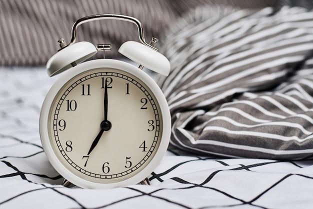 Despertador branco vintage e almofadas na cama. wale up e conceito de manhã