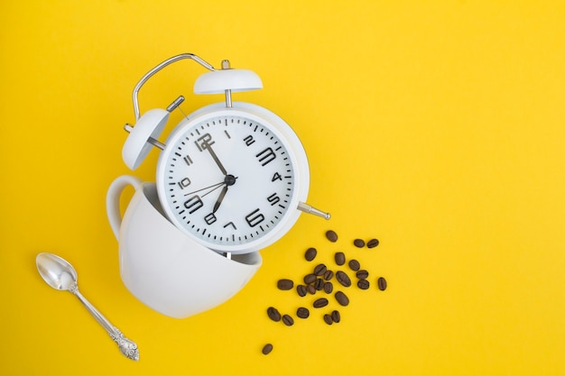 Despertador branco, xícara branca e grãos de café isolados em amarelo
