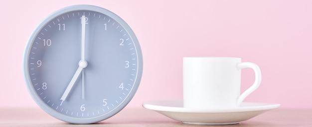 Despertador cinza clássico e copo de café branco sobre um fundo rosa, banner longo