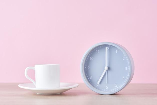 Despertador cinza clássico e xícara de café branco
