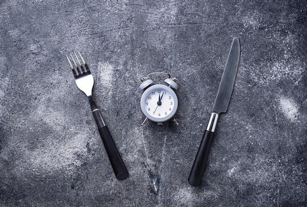 Despertador cinzento com faca e garfo