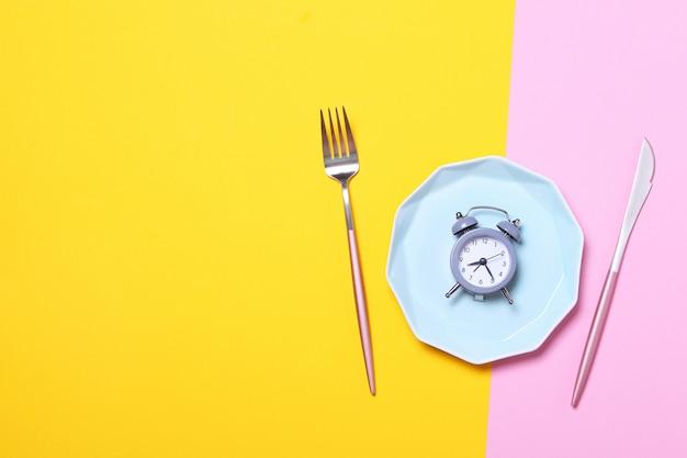 Despertador cinzento, garfo e faca na placa azul vazia em amarelo e rosa. conceito de jejum intermitente, hora do almoço, dieta e perda de peso. vista superior, configuração plana, minimalismo.