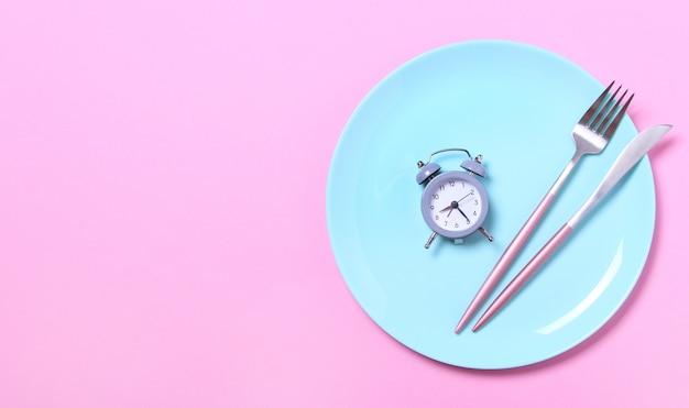 Despertador cinzento, garfo e faca na placa azul vazia no rosa. conceito de jejum intermitente, hora do almoço, dieta e perda de peso. vista superior, configuração plana, minimalismo.