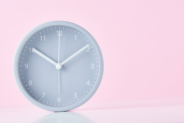 Despertador clássico cinzento em um fundo rosa pastel com espaço de cópia
