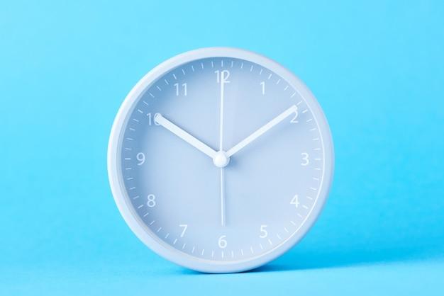 Despertador clássico cinzento sobre um fundo azul pastel, close-up