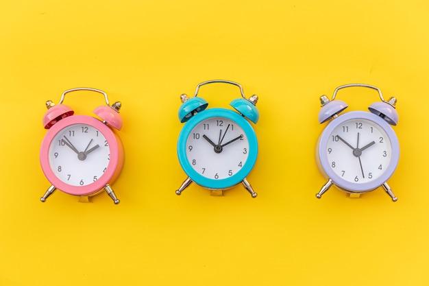 Despertador clássico de design minimalista com três campainhas gêmeas isoladas em amarelo