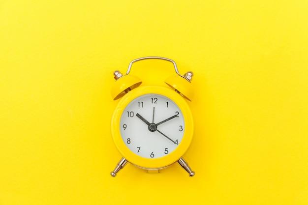 Despertador clássico do vintage do toque sino gêmeo isolado no fundo moderno na moda colorido amarelo. horas de descanso tempo da vida bom dia noite acorda conceito acordado. vista plana leiga cópia espaço.