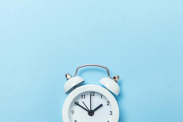 Despertador clássico do vintage gêmeo de soada do sino isolado no fundo pastel azul.