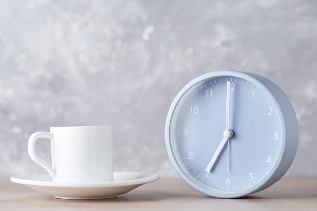 Despertador clássico e xícara de café branco em um cinza