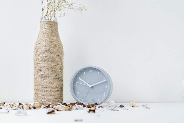 Despertador clássico, ramo de flores e pétalas em uma mesa branca.
