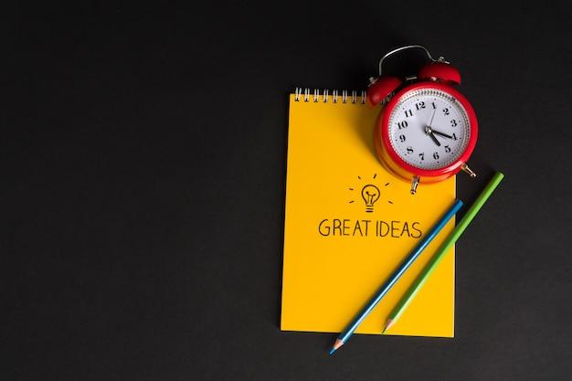 Despertador com bloco de notas e lápis de cor sobre fundo preto. volta às aulas ótimas ideias