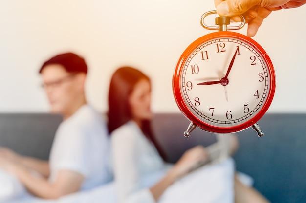 Despertador com borrão pessoas sentadas de costas para tempos de relacionamento ruim de viver juntos horas familiares ou amante de casal chato um ao outro conceito.