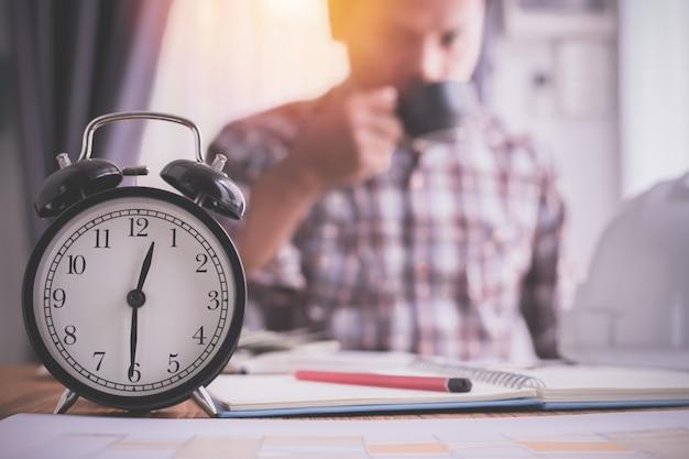Despertador com café bebendo do homem de negócios, conceito da hora de ponta.