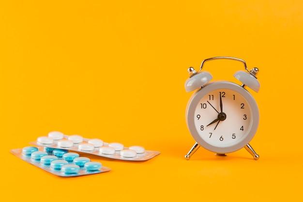 Despertador com comprimidos médicos em cima da mesa