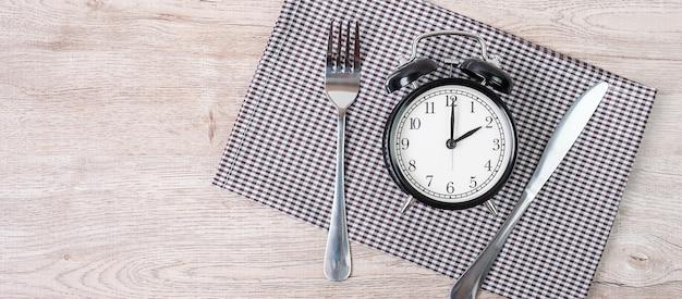 Despertador com faca e garfo no fundo da toalha de mesa