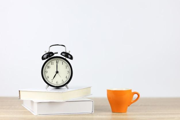 Despertador com livros e xícara de café na mesa de madeira