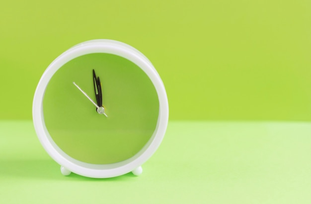 Despertador com mostrador verde sobre fundo verde