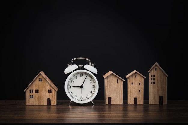 Despertador com pequena casa em madeira e fundo preto, imóveis e tempo para obter e comprar imóveis, residentes e casa
