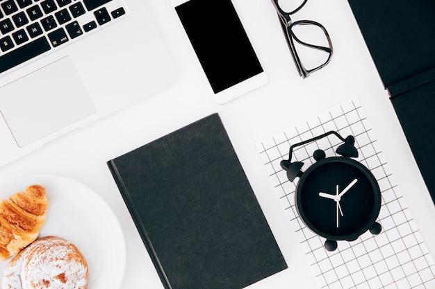 Despertador; computador portátil; celular; óculos; croissant e pãezinhos no prato e diário sobre fundo branco