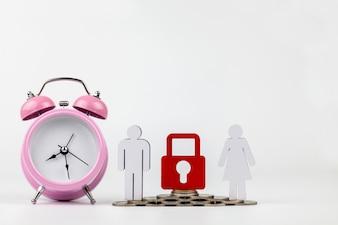 Despertador cor-de-rosa, modelo da pessoa de madeira e moeda em um de madeira no fundo branco