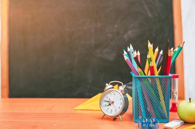 Despertador de natureza morta escolar com lápis no fundo de uma universidade do conselho escolar