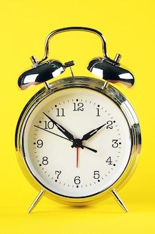 Despertador de prata de aço no estilo retro em um fundo amarelo brilhante. fechar-se.