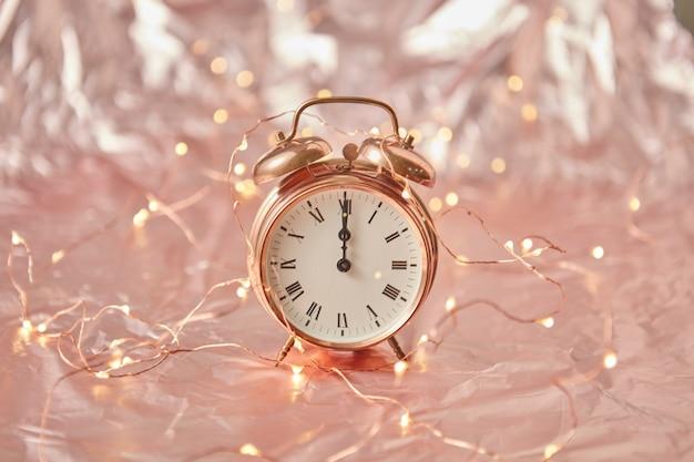 Despertador dourado com hora é meia-noite em um fundo abstrato brilhante de cobre com sequência de luzes, copie o espaço. cartão de felicitações.