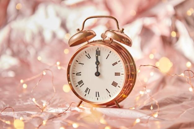 Despertador dourado com hora é meia-noite em um fundo abstrato dourado brilhante com cordão de luzes. cartão de felicitações.