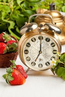 Despertador dourado velho e morangos frescos
