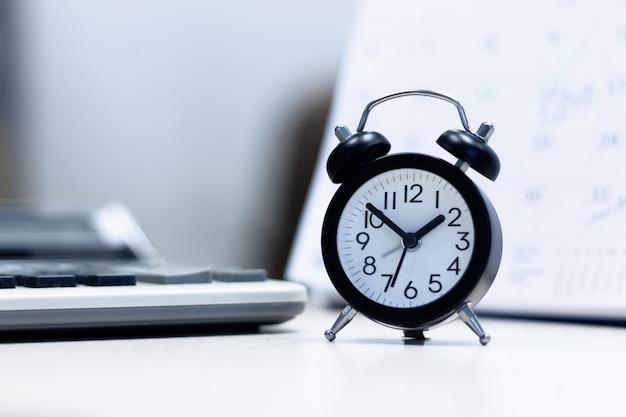 Despertador e calendário com cálculo na mesa de mesa.