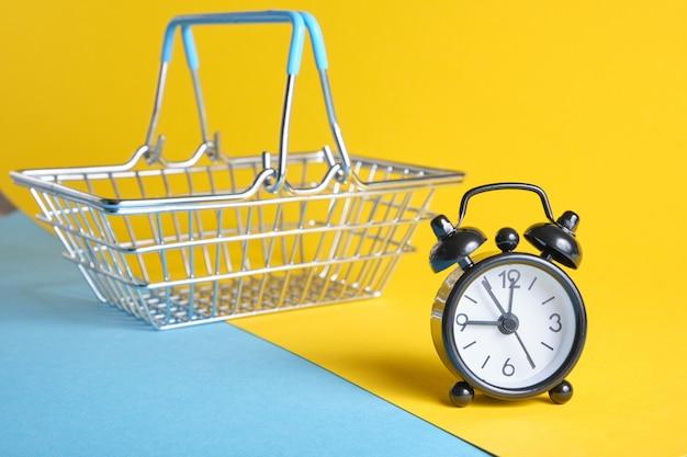 Despertador e carrinho de compras em miniatura em fundo amarelo