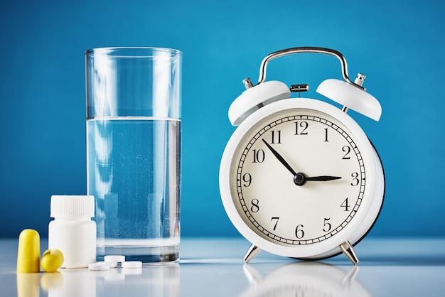 Despertador e copo de água com comprimidos