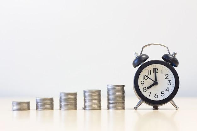 Despertador e dinheiro moeda pilha na mesa de mesa
