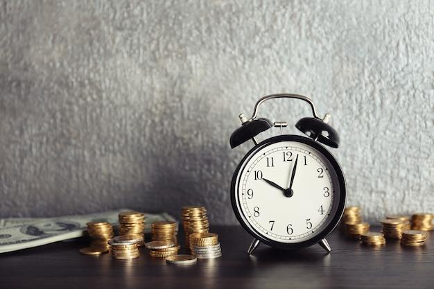 Despertador e dinheiro na mesa de madeira