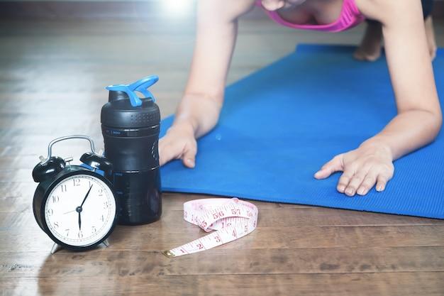 Despertador e fita métrica e jovem yoga asiática em casa em segundo plano, elaborando e conceito de estilo de vida, foco seletivo