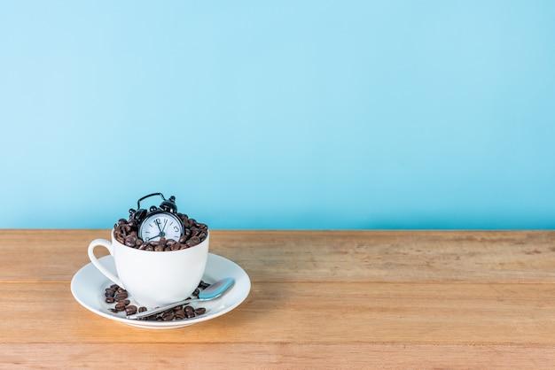 Despertador e grãos de café em copo branco na mesa de madeira