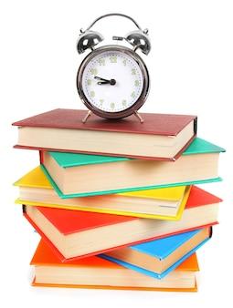 Despertador e livros multicoloridos em branco.