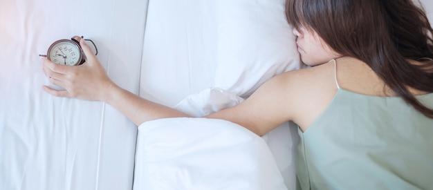 Despertador e mão de mulher asiática parar o tempo na cama enquanto dorme, fêmea adulta jovem acorda tarde da manhã. relaxe fresco, sonolento e tenha um bom dia conceitos