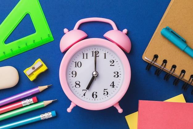 Despertador e material escolar em uma superfície azul