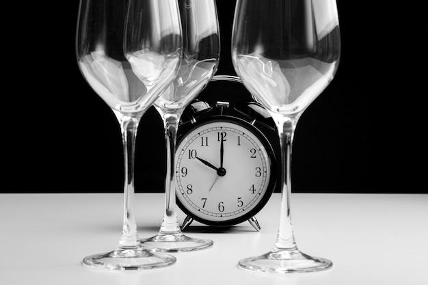 Despertador e taças de vinho vazias