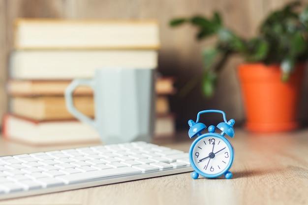 Despertador e teclado em cima da mesa de escritório. conceito de escritório, dia de trabalho, pagamento por hora, horário de trabalho.