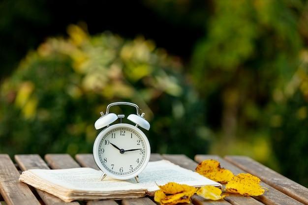 Despertador e um livro sobre uma mesa em um jardim de outono