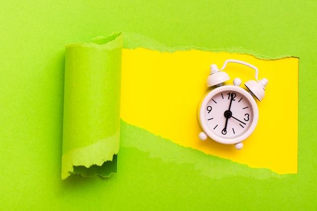 Despertador em um buraco no papel verde. conceito de falta de tempo