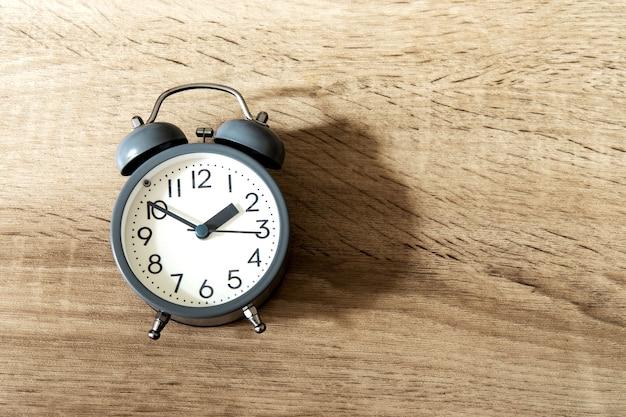 Despertador em um fundo de madeira brilhante, conceito de gerenciamento de tempo