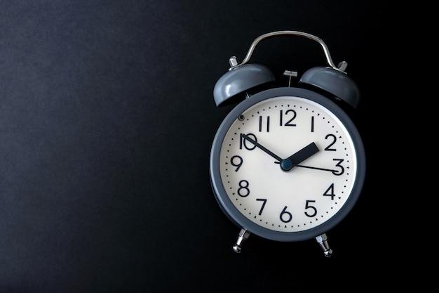 Despertador em um fundo preto brilhante, conceito de gerenciamento de tempo