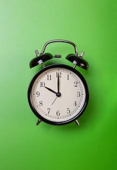 Despertador em um fundo verde
